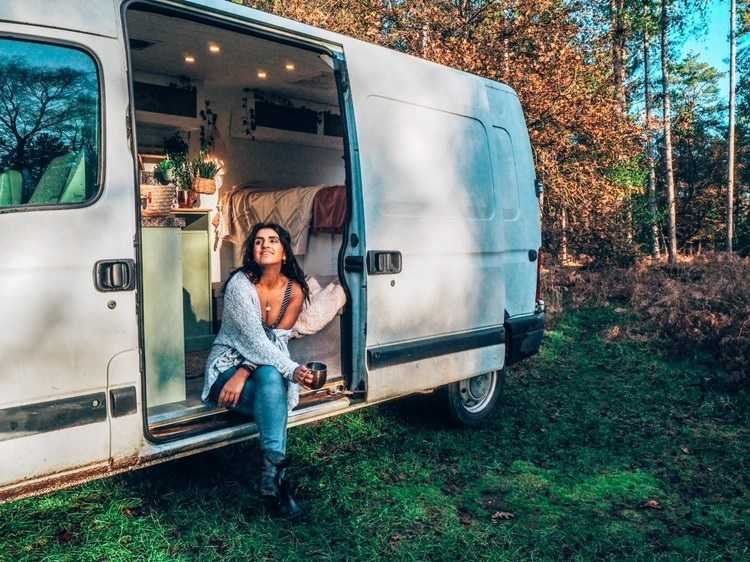 A woman (Absolutely Lucy) sits in the open doorway of her van. The picture is taken in a woodland - the van is parked on the grass. Inside the van can be seen fabrics and storage space.