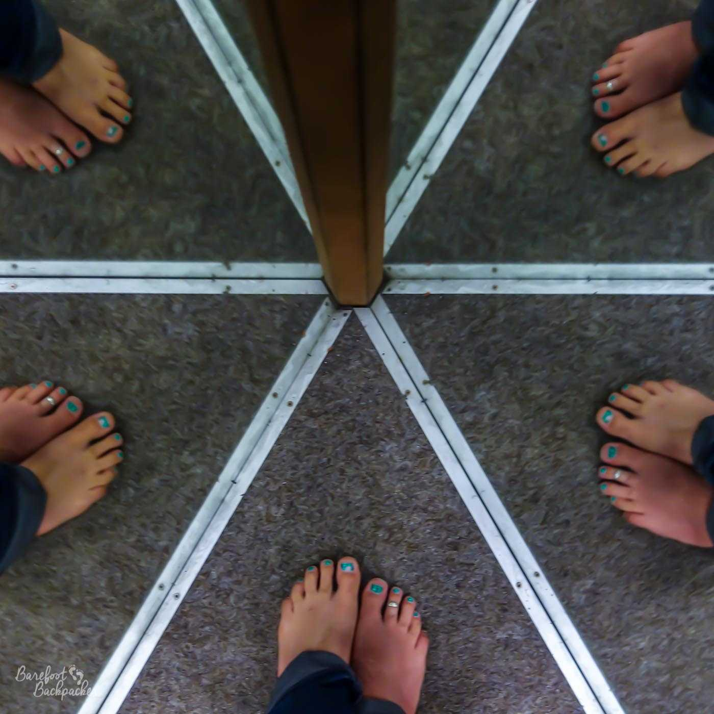 On a grey carpet with a pole in the centre of shot, there appear to be five sets of bare feet each separated by a couple of metal rails. In reality it's a small passageway made up with mirrored walls and four of the feet and rails are mere reflections.
